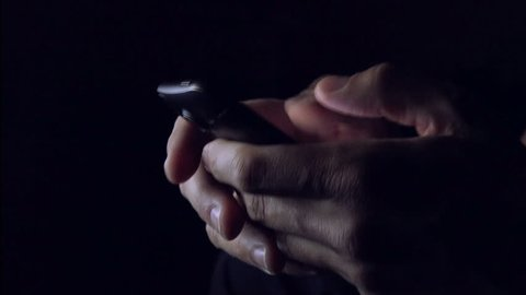 Man sending SMS text message on smartphone in dark room, close up of hands and mobile phone