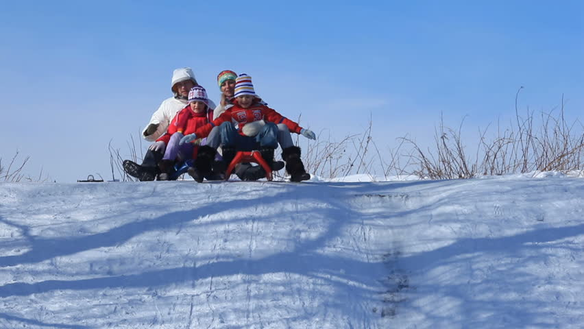 Happy parents and their children riding on sleds in winter