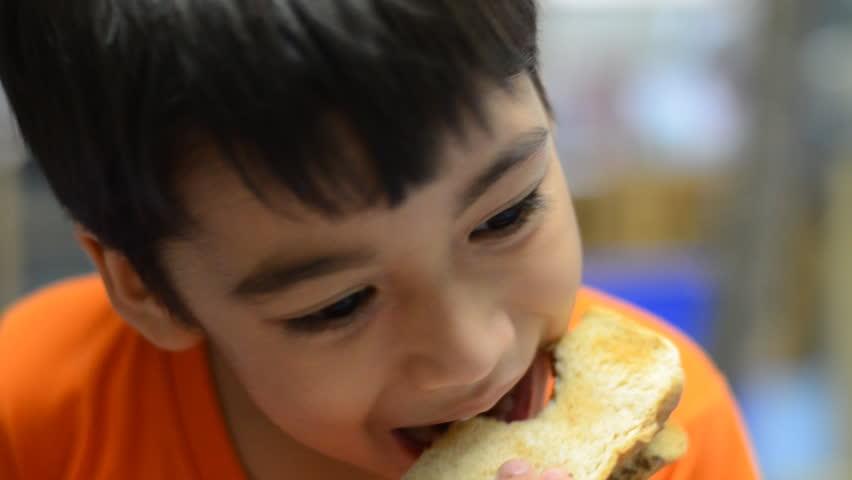 Little boy eating bread with happy face   Shutterstock HD Video #10951859