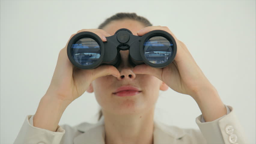 Tilt up image of young businesswoman using binoculars. Female professional is searching for opportunities. Executive is standing against wall.