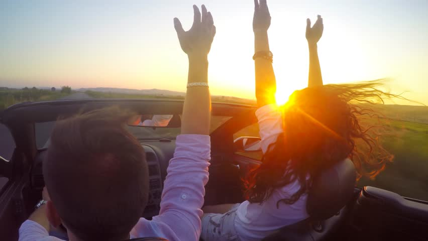 Close up of party couple with hands up, driving convertible, car, at sunset with sun flare. Steadicam shot.. UHD 4K stock footage #10953380