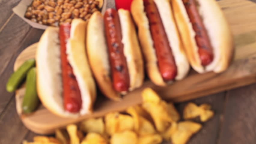Grilled hot dogs on a white hot dog buns with chips and baked beans on the side. | Shutterstock HD Video #10961864
