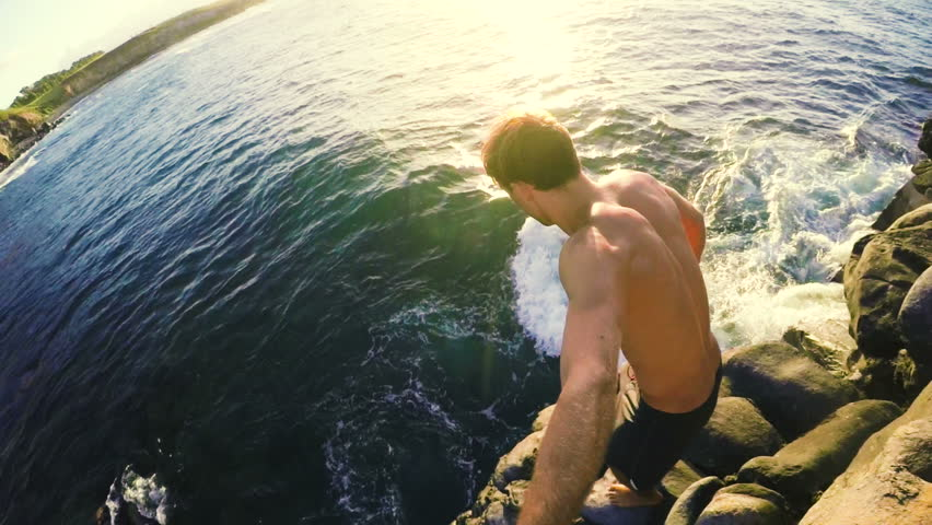 GOPRO POV of Athletic Young Man Jumping from Sea Cliffs into the Blue Ocean in Hawaii at Sunset.