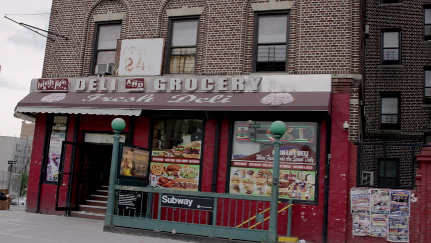 NEW YORK - JULY 12, 2015: corner deli on the Grand Concourse in the Bronx, driving past Tremont Ave, 4K, NY. The Bronx is the north-most borough of NYC.