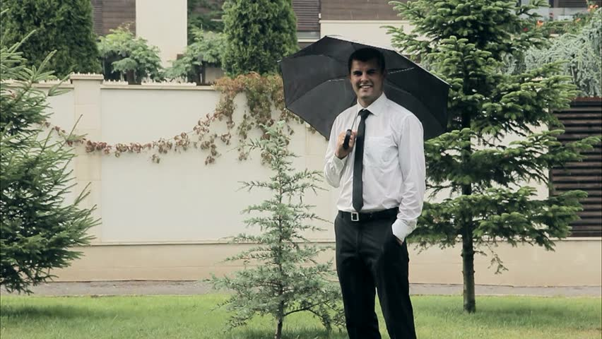 Content Businessman With Umbrella Smiling in the Summer Rain