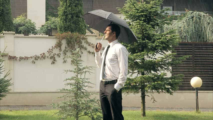 A Businessman With Umbrella is Smiling in the Summer Rain Prosperity Concept