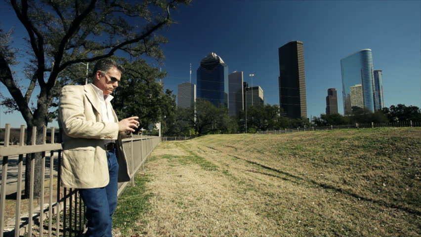 An attractive mature man standing against the fence of a downtown green space talks on his smart phone with metropolitan Houston looming in the background.