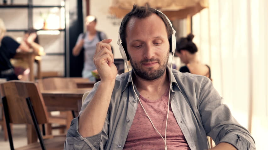 Young happy man in earphones listen to the music in cafe  | Shutterstock HD Video #11025992