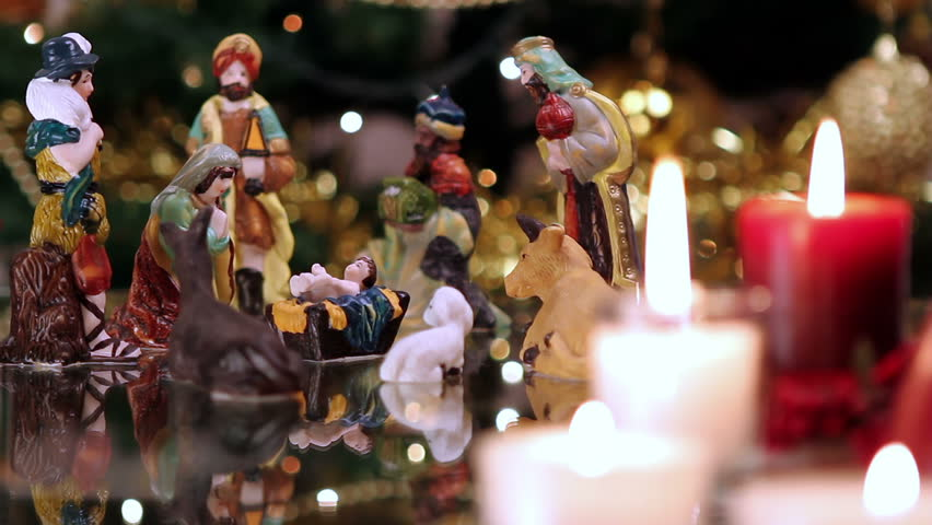 Christmas nativity scene with candles in front of Christmas tree. The focus moves from candles to figurines.