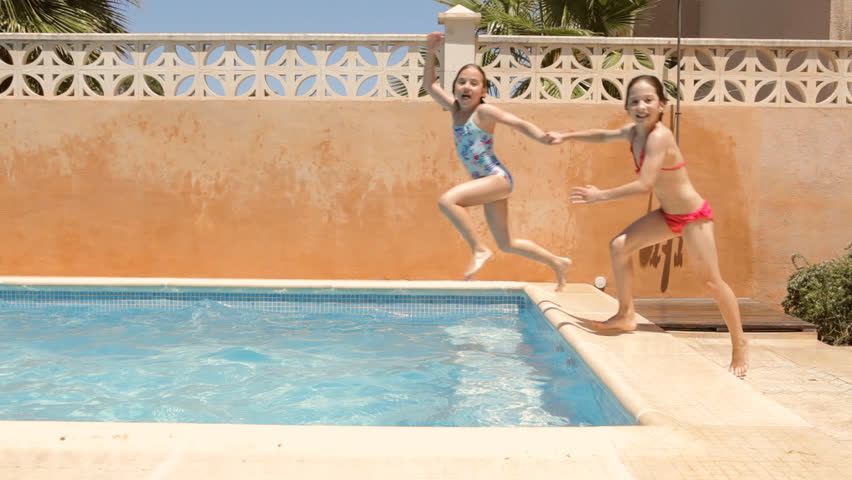 Four children friends playing and jumping into a home garden swimming pool on a sunny summer holiday day, exterior. Kids playing together in water, outdoors swimming pool.