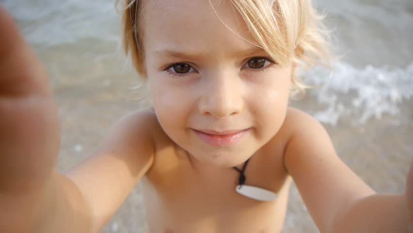 A cute little child video chats on smart phone on the beach on blue sea background. Using a portable handheld device on summer vacation. Talking on a mobile. Doing selfie. Wide angle view #11046518