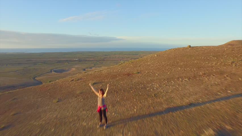 AERIAL: Flying around the cheerful woman raising hands on top of the mountain | Shutterstock HD Video #11070443