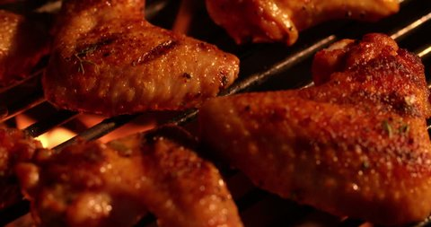 Spicy chicken wings grilling slowly over glowing coals at a night time barbecue in Slow Motion