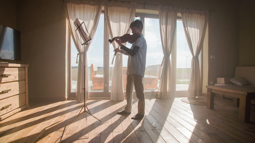 Playing violin in beautiful home room with sun shining 4K. Inside dream-like home with beautiful shiny background big windows and view on landscape. Boy playing on violin in front of windows. Retro.