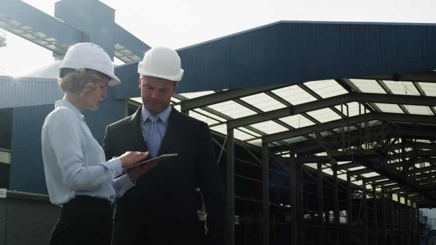 Managers in Hard Hats are Talking and Using Tablet PC in Industrial Environment. Shot on RED Cinema Camera in 4K (UHD).