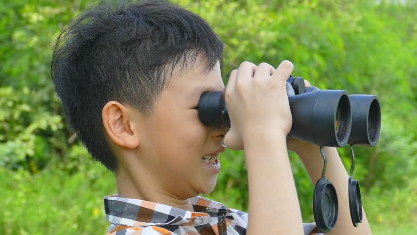 Asian boy looking through binoculars in garden
