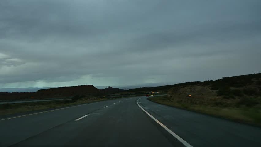 SAN RAFAEL DESERT, UTAH - JULY 2015: Point of View looking forward while driving the San Rafael desert of Utah following a summer rain as night starts to fall. | Shutterstock HD Video #11102696