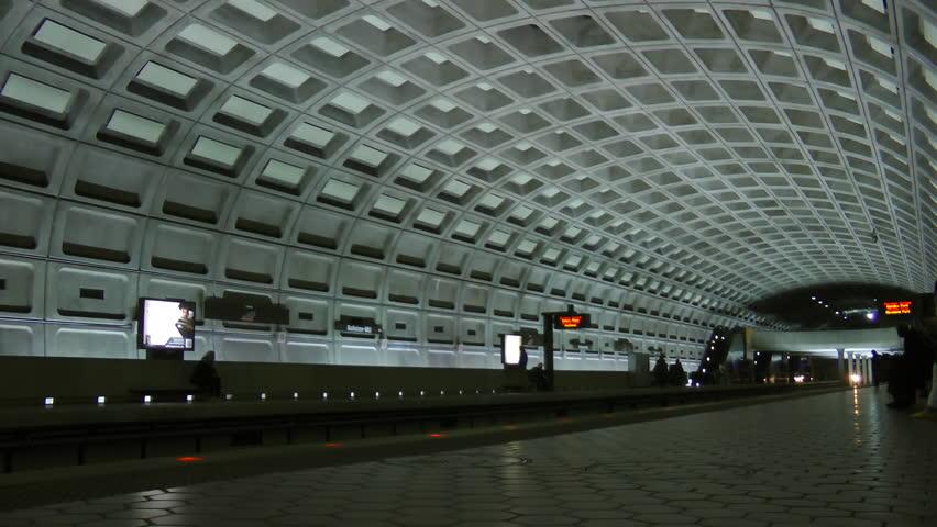 WASHINGTON, DC - APRIL 2013: DC Metro subway trains arrives opposite platform, commuters exit, at busy Ballston station in suburban Arlington, Virginia.