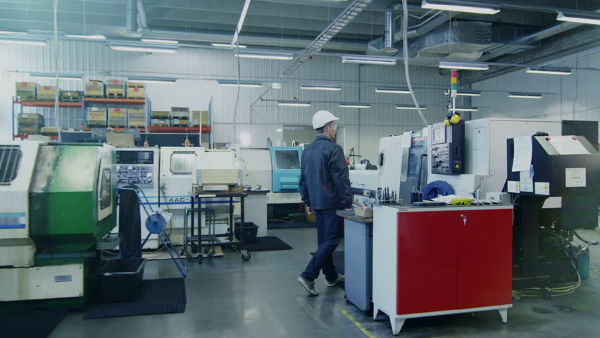 Factory Worker in Hard Hat is Setting Up CNC Lathe Machine