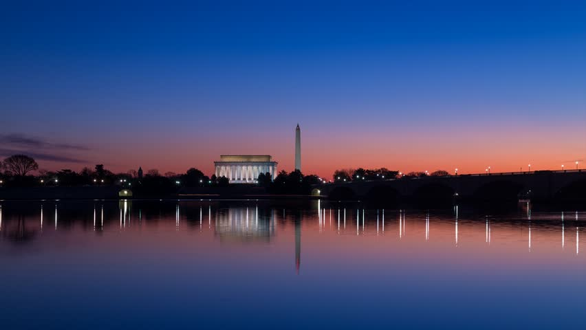 Time lapse of a sunrise on the Lincoln Memorial and Washington Monument as seen across from the Potomac River.