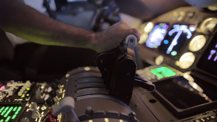 Detail shot of airline pilot pushing throttle forward in the cockpit of a jumbo jet.  Side view, hand-held camera, originally recorded in 4K.
