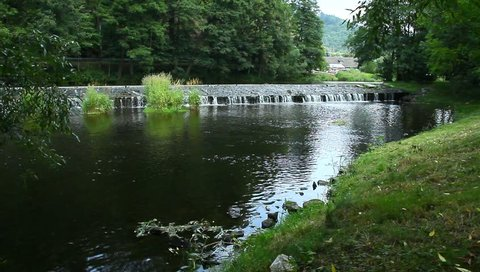 outlet sluice on a river, beautiful summertime with green trees and plants