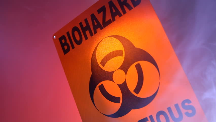 A close up of a biohazard warning sign with smoke coming into and out of the frame, and flashing warning lights reflected on the sign
