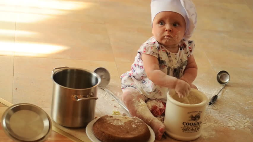 A little cute ten-months-baby-girl with cooking hoods on her head is sitting on the kitchen floor, she is heavily soiled with wheat flour - she's playing cook | Shutterstock HD Video #11174801