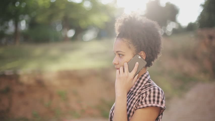 Attractive african american business woman commuter using smartphone walking in city at sunset