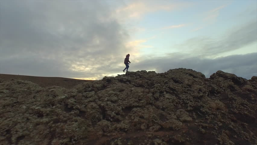AERIAL: Young woman hiking up on the edge of volcanic crater in autumn evening | Shutterstock HD Video #11208305