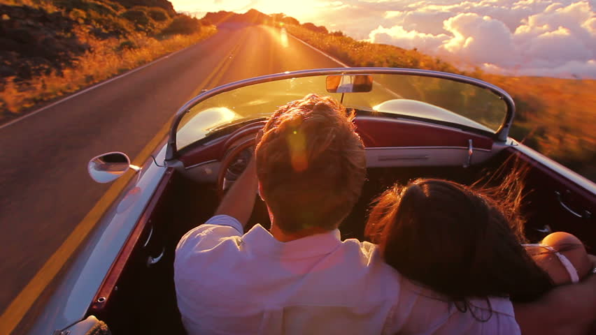 Happy Couple Driving on Country Road into the Sunset in Classic Vintage Sports Car. Steadicam Shot with Flare. Romantic Freedom Love Concept. #11215373