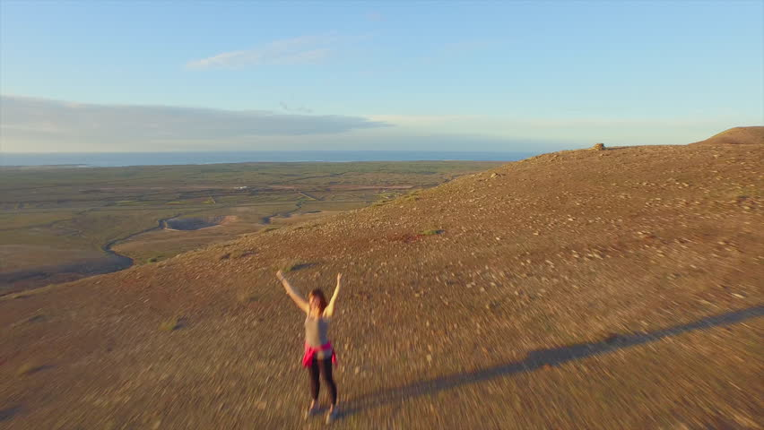 AERIAL: Flying over cheerful woman raising hands on volcanic mountain peak | Shutterstock HD Video #11215934