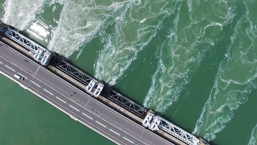Best Selling HQ Aerial Drone Video (Ultra HD) of the famous Dutch Delta Works. Sunny weather. Opened barriers while traffic passing by. 90 degrees Angle with rotation.