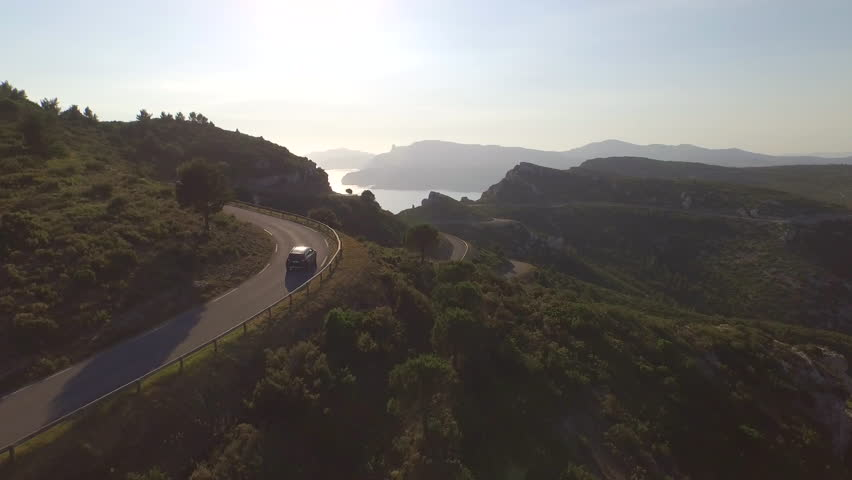 AERIAL: Flying above SUV jeep driving over mountain pass road towards the beautiful sunny ocean