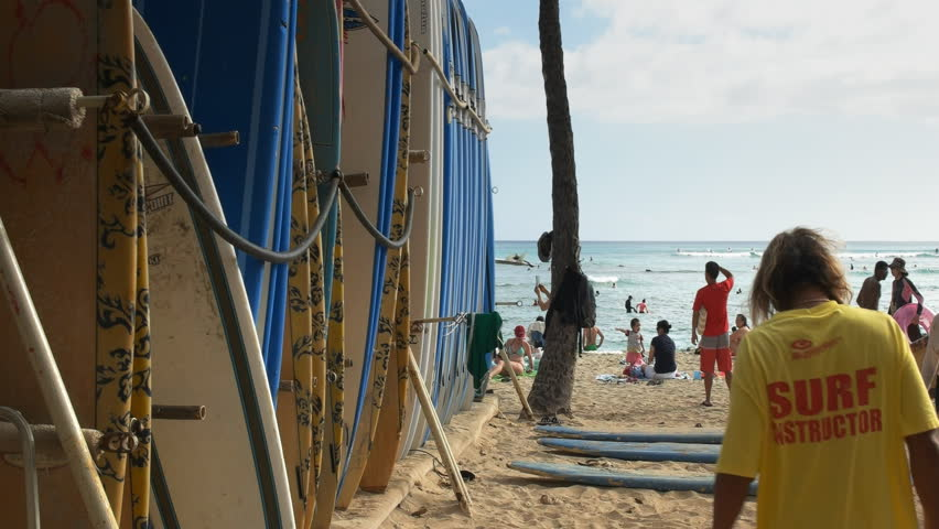 HONOLULU, UNITED STATES OF AMERICA - AUGUST 6 2015: a number of rental surfboards and a beachboy at waikiki, hawaii