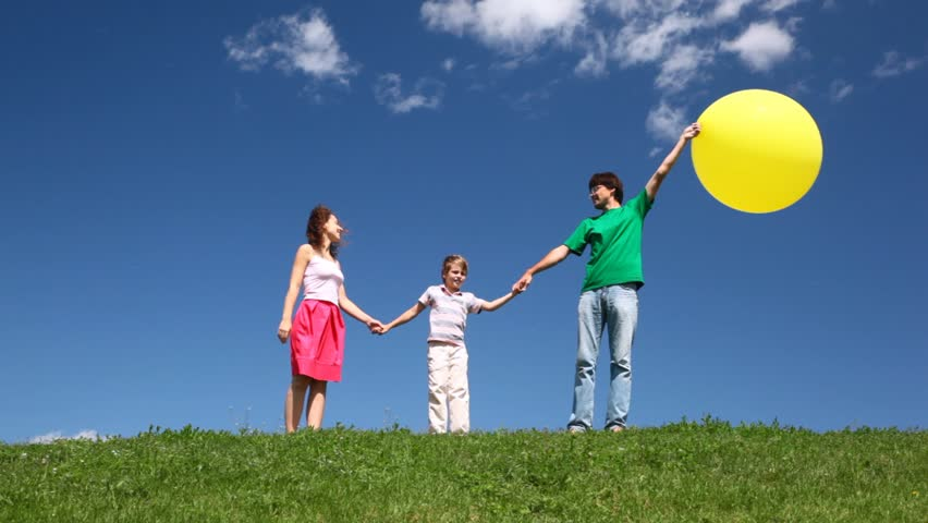 Happy family of three with yellow balloon on hill with green grass and wildflowers  | Shutterstock HD Video #1132867