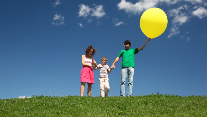 Family of three holding yellow balloon hands down hill with green grass and wildflowers  | Shutterstock HD Video #1132870