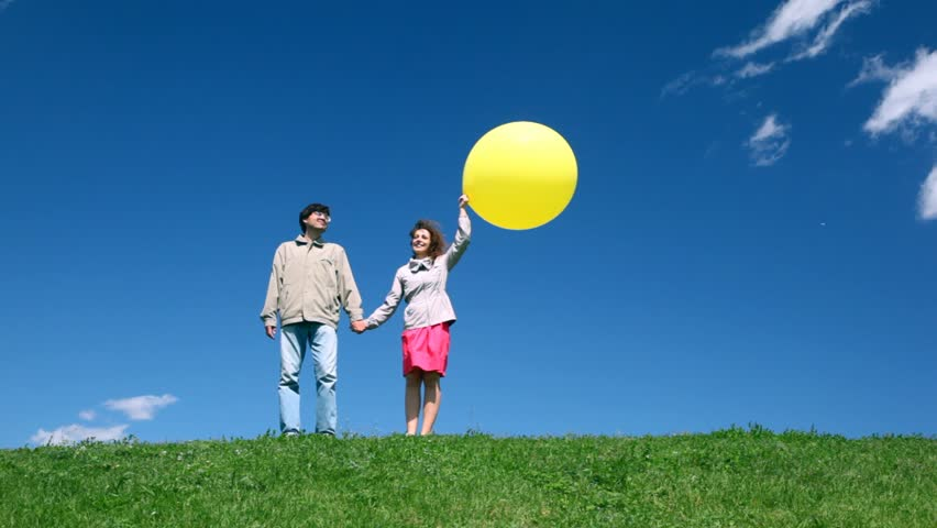 Man and woman holding hands with yellow balloon walk on hill | Shutterstock HD Video #1132888
