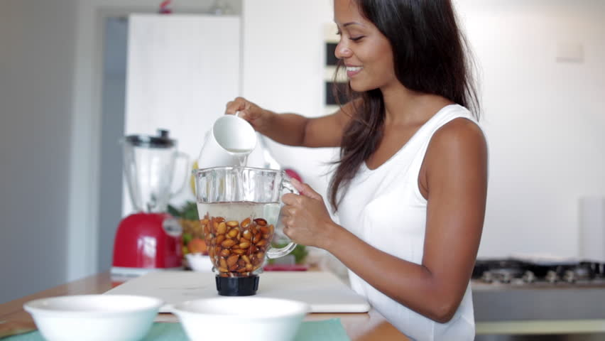 Young woman adding water to make almond milk