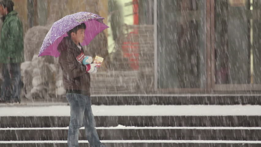 Shenyang, China - December 2010: A Chinese boy waiting on the street with an umbrella as heavy snow falls in Shenyang, Liaoning Province, China. | Shutterstock HD Video #11336741