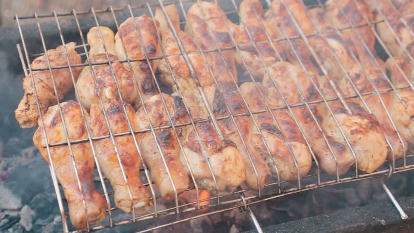 Delicious grilled chicken drumsticks cooked on smoldering coals on the barbecue outdoors | Shutterstock HD Video #11353760