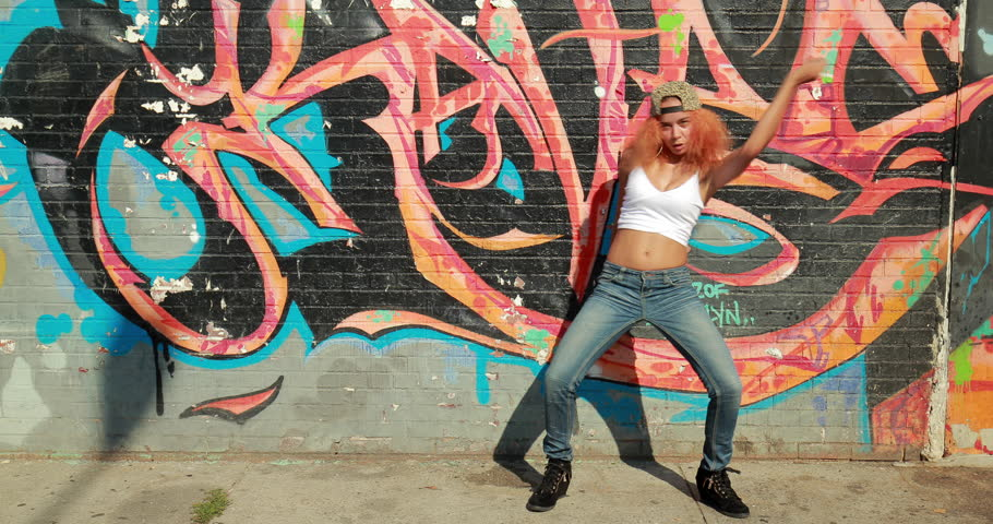 Young Latina woman in New York City dancing in front of graffiti wall background | Shutterstock HD Video #11355479