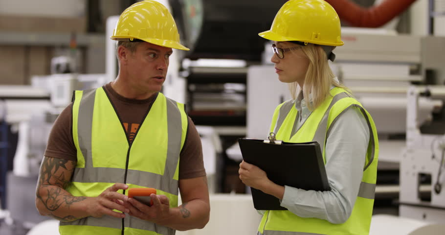 An attractive businesswoman talking to her line manager at a shipping warehouse | Shutterstock HD Video #11357195