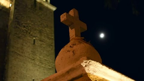 Focus and low angle shot on cement cross at night with moon in background and old colonial cathedral in Valladolid, Mexico