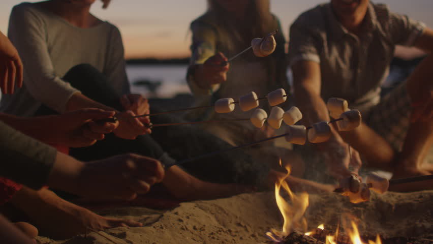Group of People near Campfire Frying Marshmallows at Night. Shot on RED Cinema Camera in 4K (UHD). #11364341