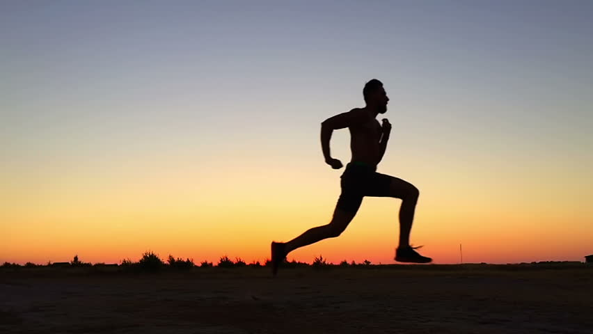 SLOW MOTION: Running man silhouette in sunset time | Shutterstock HD Video #11373104