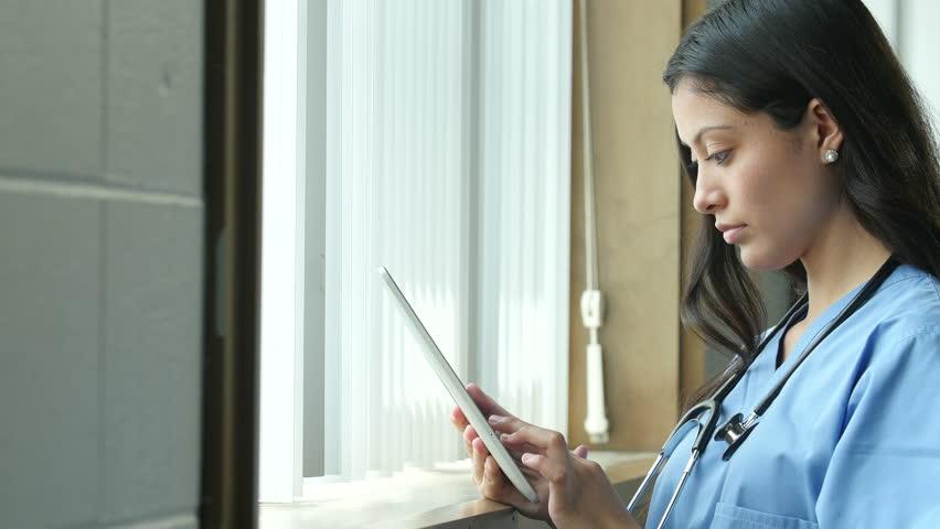 Young hispanic nurse using an ipad in a medical setting