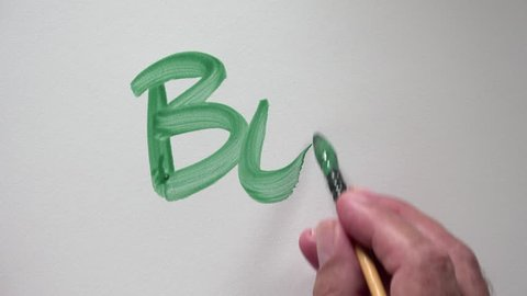 """Human hand writing word """"BUT"""" with green gouache"""