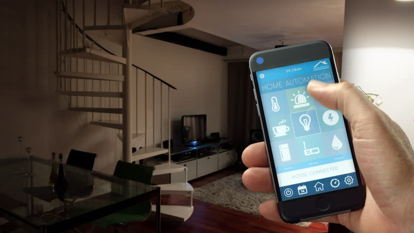 Smart Home - smart house, home automation, device with app icons. Man uses his smart phone with smarthome security app to turn on the lights of his house. (Shot on RED)