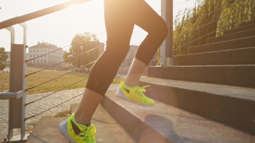Woman feet jogging up stairs, close up. Steadicam stabilized shot. Slow Motion. Sportswoman wearing barefoot sports shoes while training on the sunny stairs. Lens Flare. | Shutterstock Video #11427086